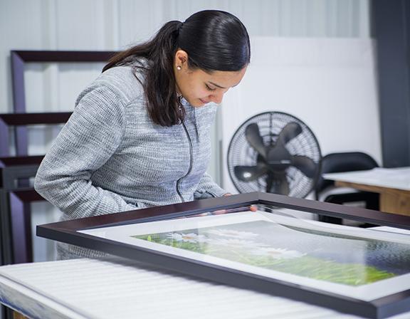 craftswoman at Framed It building a custom frame